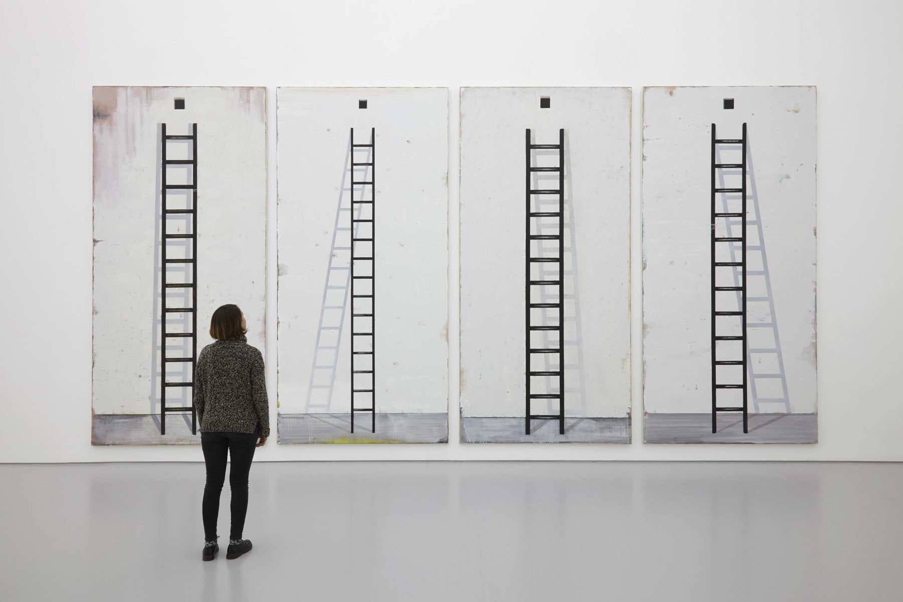 A visitor stands looking at four tall paintings of ladders. Each painting has a shadow appearing differently behind the ladder.