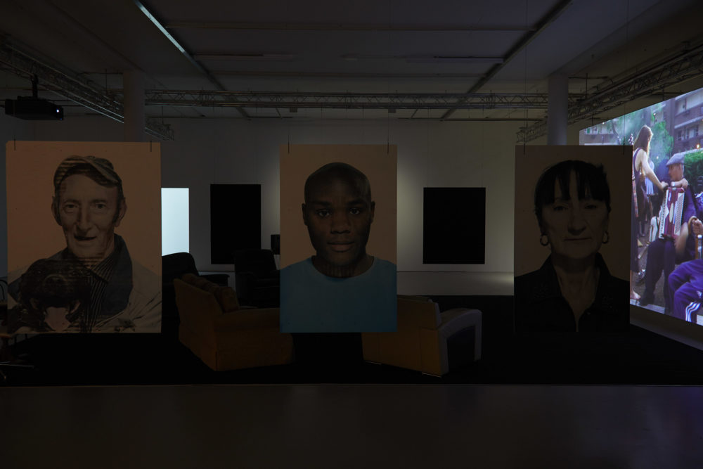 Large portraits of people involved in the project hang from the ceiling, marking a barrier between the gallery walkway and a viewing area with sofas in, pointed at a large screen, currently showing a man playing an accordian.