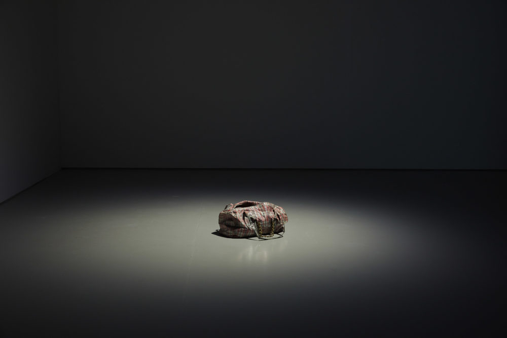 A gym bag, made from the material used on laundry bags, is placed on the floor of the gallery and lit by a spotlight.