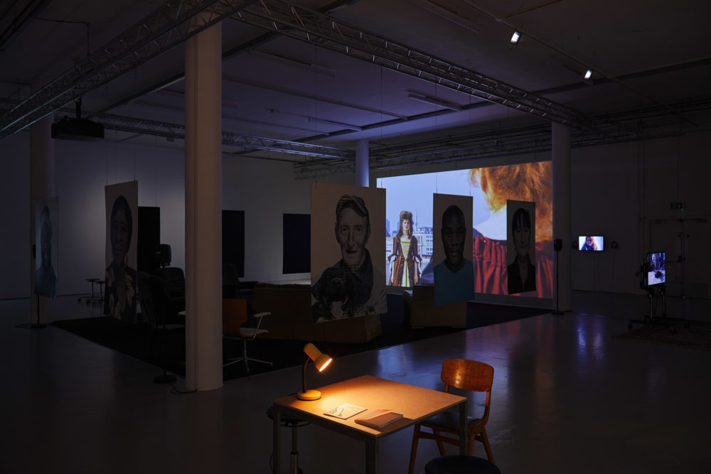 In the foreground a desk is illuminated by an angle poise lamp. Behind the desk are portraits that are hanging from the ceiling.