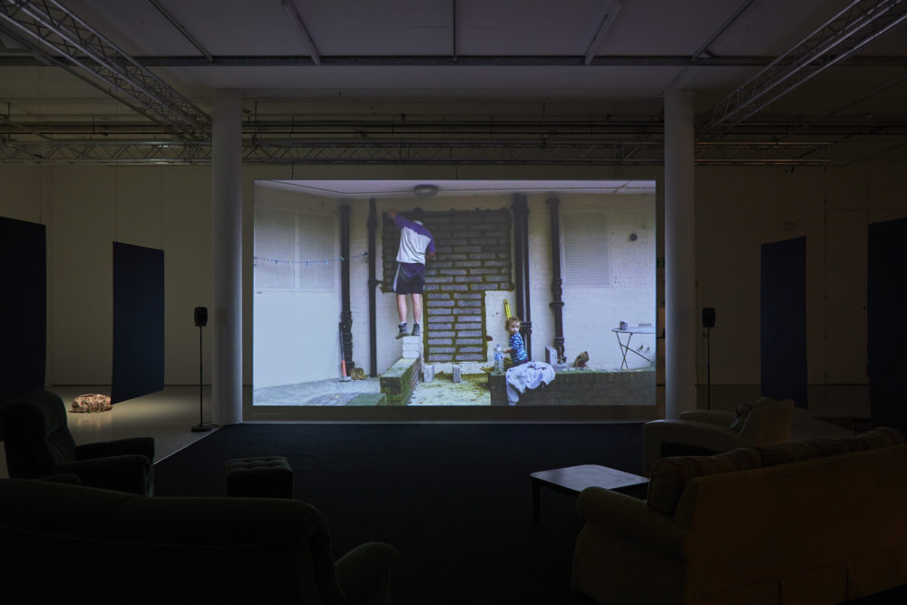 A projection of a man bricking up a doorway hangs in the gallery. Plush sofas and arm chairs point at the projection.
