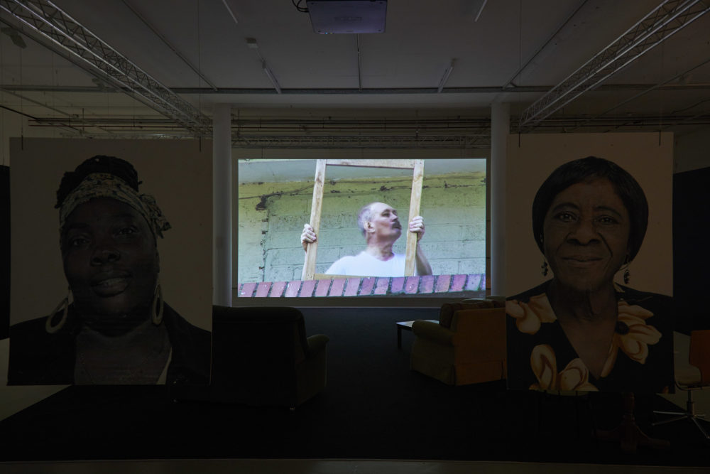 Two large portraits of women involved in the project hang from the ceiling, marking a barrier between the gallery walkway and a viewing area with sofas in, pointed at a large screen, currently showing a man carrying some furniture on a balcony.