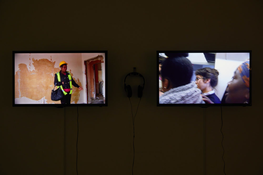 Two flat screen televisions are placed in a gallery - with headphones hung up on a hook between them. The left screen shows a woman wearing a hi-vis vest and points at an empty door frame that looks like its mid construction. The right screen shows three women stood closely with one another - you can only see their shoulders and their heads.