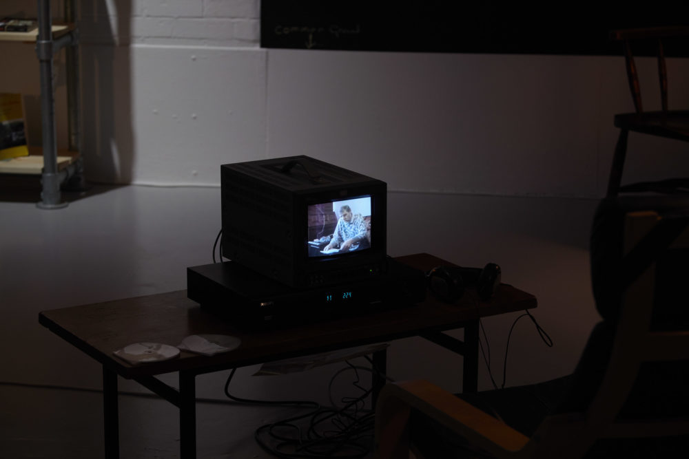 A small television screen in the galleries sits atop a table, a lounger chair can just be seen in the bottom right foreground of the image.