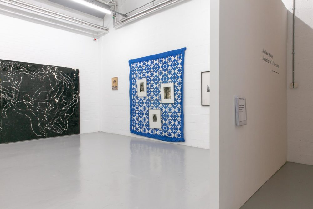 The white corner gallery houses a large black painting of dancers and a large blue and white patchwork quilt.