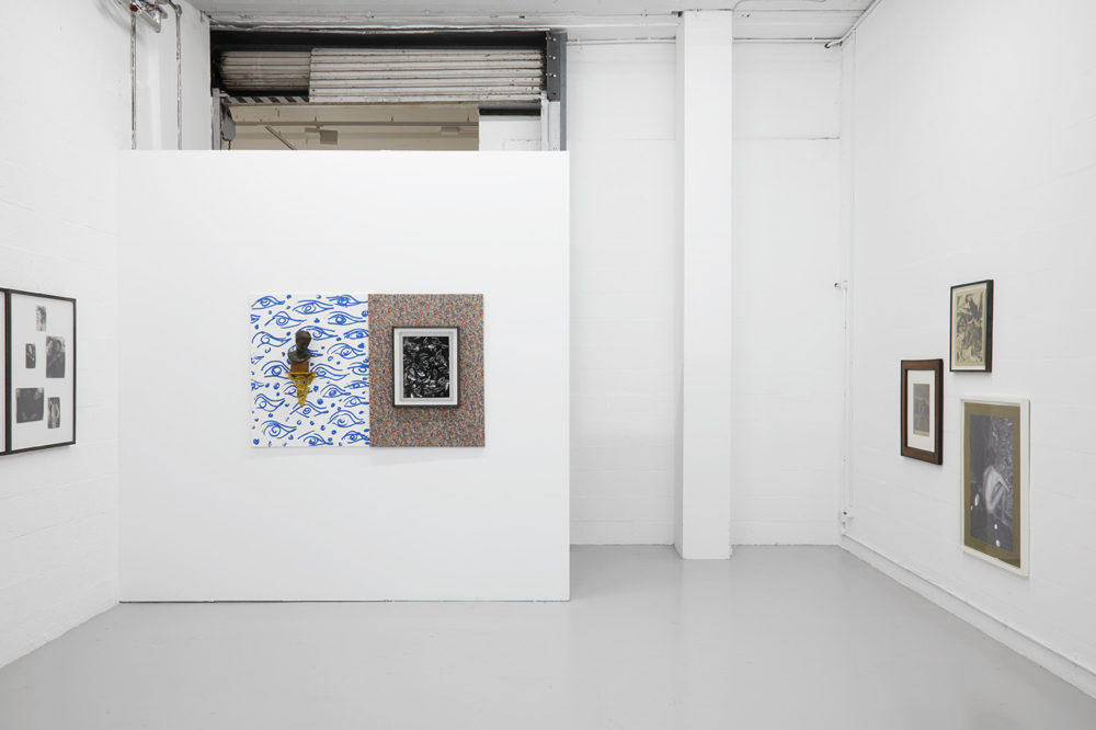 Various differing images hang on the white walls of the gallery space.