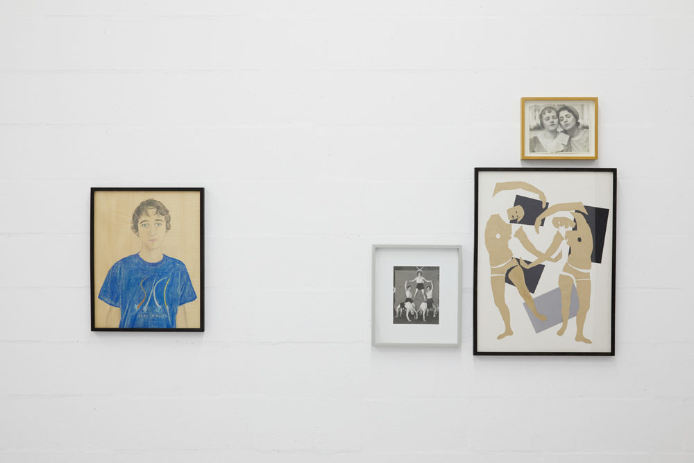 Four framed pictures hang next to one another. On the left, a pencil drawing of a young man. On the right, a triptych of pictures of performers.