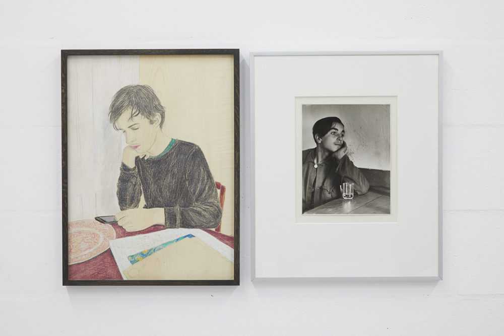 Two framed pictures hang next to one another. On the left, a pencil drawing of a young man sat at his table and looking at his phone. On the right, a photograph of a young person sat at a table with a glass of water.