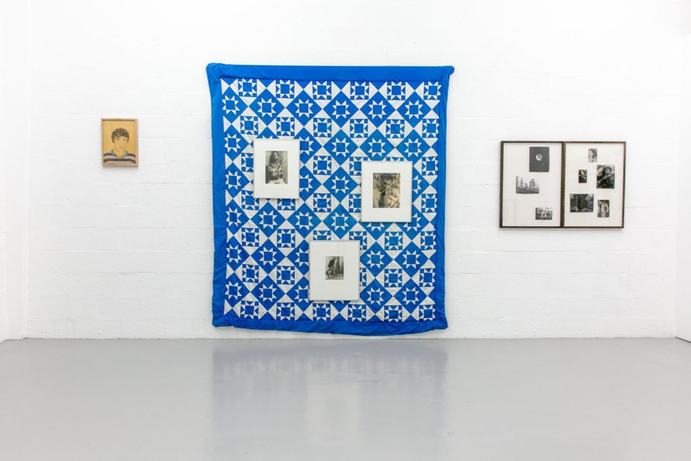 A blue and white patchwork quilt made up of diamond, squares and triangle shapes, hangs on a white gallery wall. Six frames are also hung on that wall - three on top of the patchwork quilt.