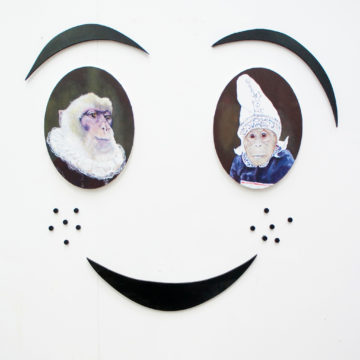 Assemblage piece: Overall, the piece looks like a cartoon smiling face. The eyes are made from two portraits of monkeys wearing human clothes.