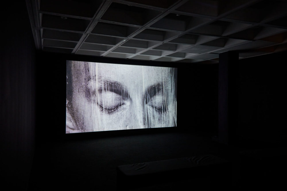A piece from Basin Magdy, The Stars Were Aligned for a Century of New Beginnings (2017) at Arnolfini. A projection of a man's face as water pours down it.