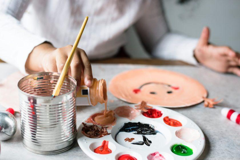 A paint palette is being filled by a young child whose hand is in the foreground and in focus, but whose body is out of focus in the background. They have painted a plate with a smiley face.
