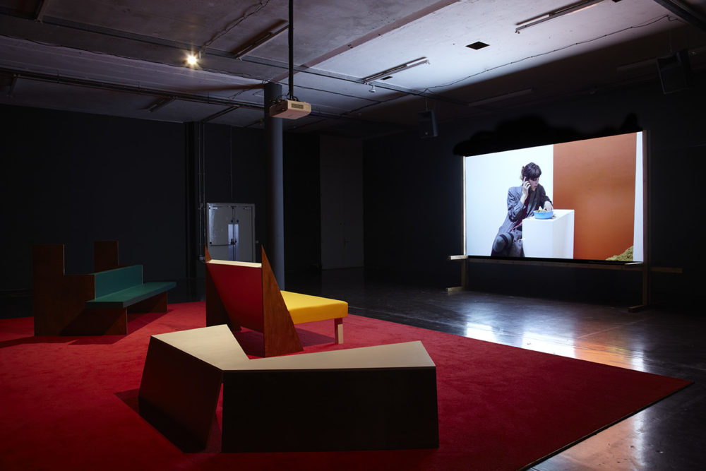 Installation view of Cara Tolmie, Pley (2013). Angular furniture, is illuminated in front of a film. The screen currently shows a seated woman making a phonecall.
