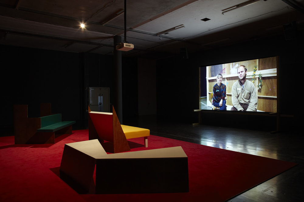 Installation view of Cara Tolmie, Pley (2013). Angular furniture, is illuminated in front of a film. The screen currently shows a man and a woman sitting facing forward.