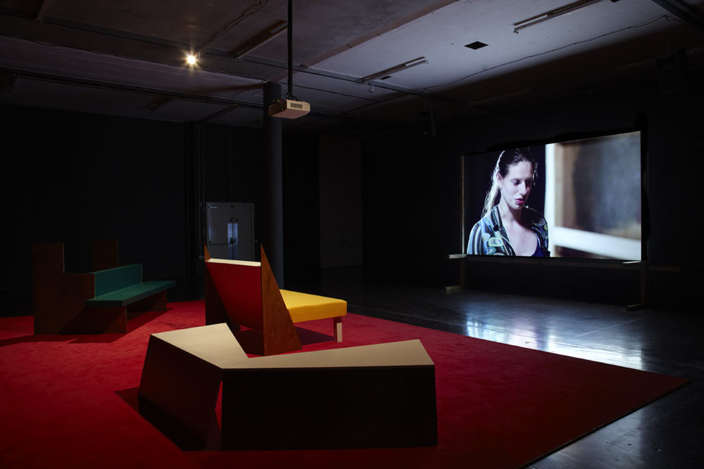 Installation view of Cara Tolmie, Pley (2013). Angular furniture, is illuminated in front of a film. The screen currently shows a close up of a woman.