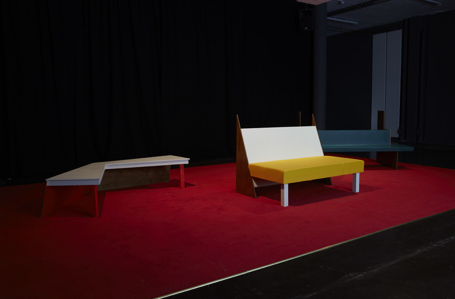 Installation view of Cara Tolmie, Pley (2013). Angular colourful furniture sits spotlighted in a dark room.