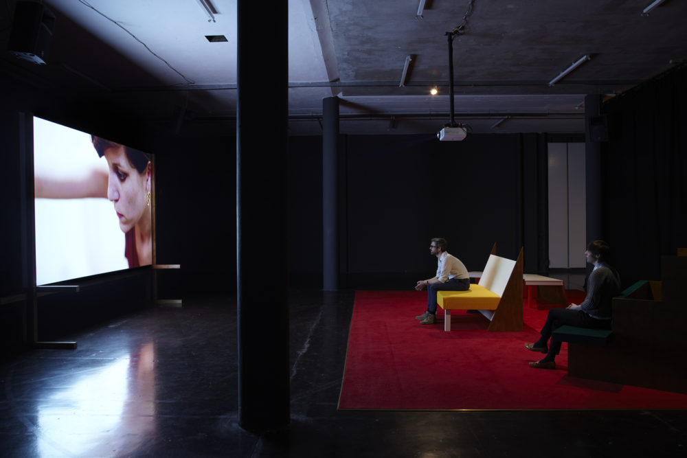 Installation view of Cara Tolmie, Pley (2013). Two visitors sit on angular furniture, watching a film. The screen currently shows a close up of a woman.