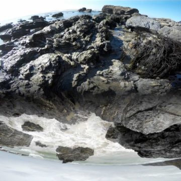 A manipulated photograph of a rocky outcrop that appears to have been bent in two - water pools on top of the rocks and crashes on the bottom side.