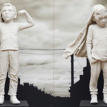White porcelain statues of young children dressed as superheroes. On the left, a child is wearing a cape and holds their arms up, flexing their biceps. On the right, a child has their hands in their pockets and they look downcast. These statues are placed in front of a black and white image of a suburban street.