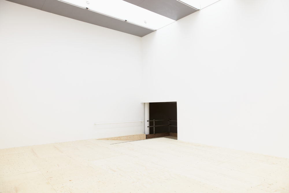 Installation: The white, empty looking gallery is taken from an angle so you can see the entrance.