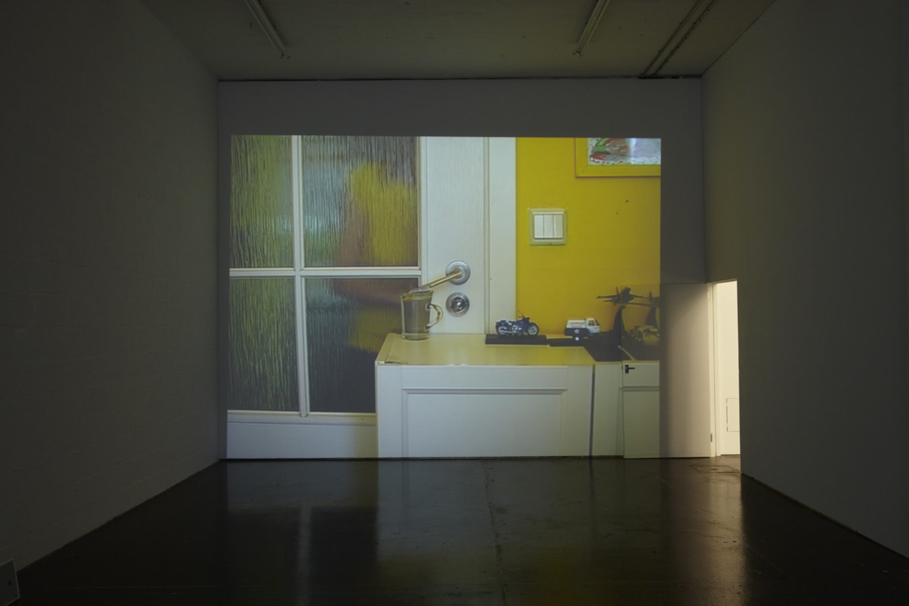 Installation view of Cezary Bodzianowski, Tea Back (2011). A projection of a domestic scene.