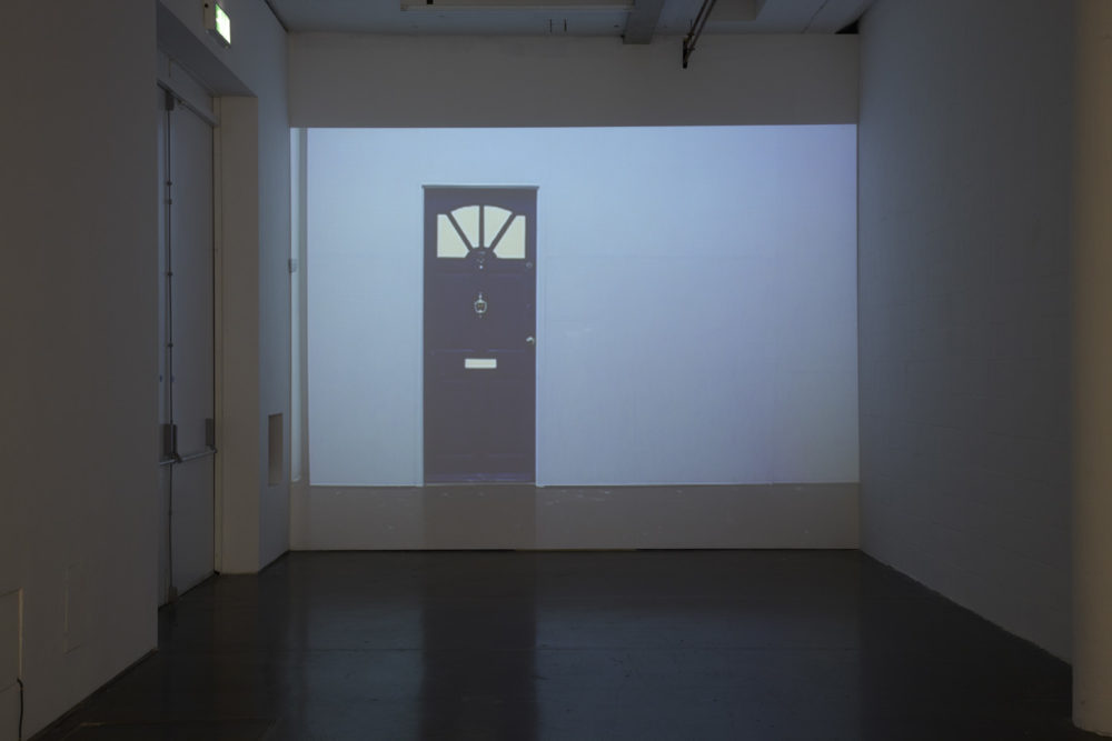 Installation view of Cezary Bodzianowski, Tea Back (2011). A projection of another part of the exhibition is screened onto a wall.