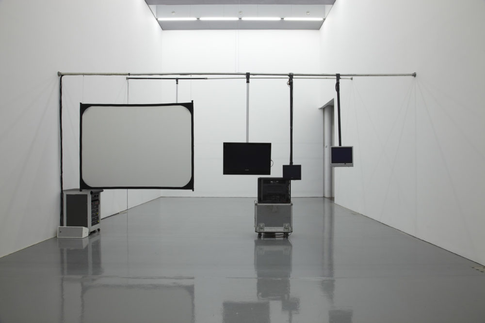 Installation view of Cezary Bodzianowski, Tea Back (2011). A bright white room shows five screens, nothing shows on the screens.