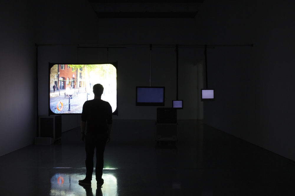 Installation view of Cezary Bodzianowski, Tea Back (2011). A visitor stands in a dark room, looking at a projection of Bristol Harbourside.