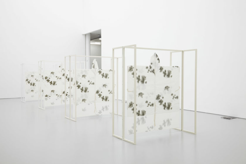 Four white wooden free standing structures stand in the middle of the white gallery. White fabric decorated with dark patches is stretched onto the frames.