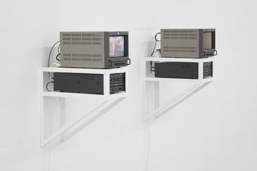 Two small but boxy screens sit on white wooden shelves, held up by white brackets on a white gallery wall.
