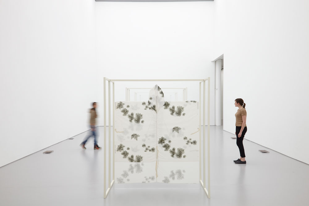 A white wooden free standing structure stands in the middle of the white gallery. White fabric decorated with dark patches is stretched onto the frame.