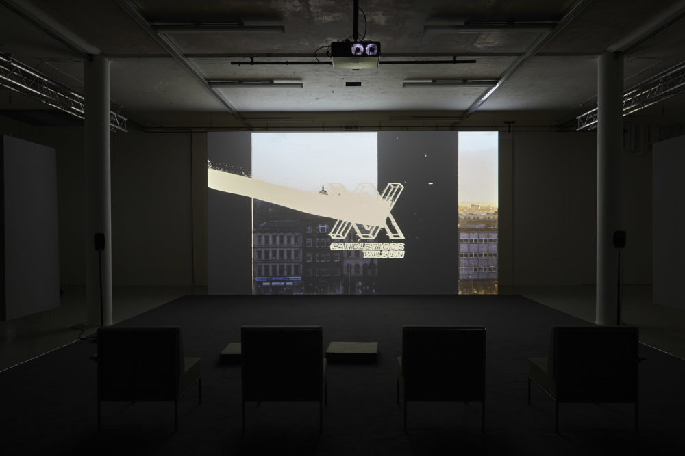 Four large chairs sit on a carpet square in the middle of the gallery. They face a screen that is currently showing a scene of a busy street with an XX logo showing over the image.