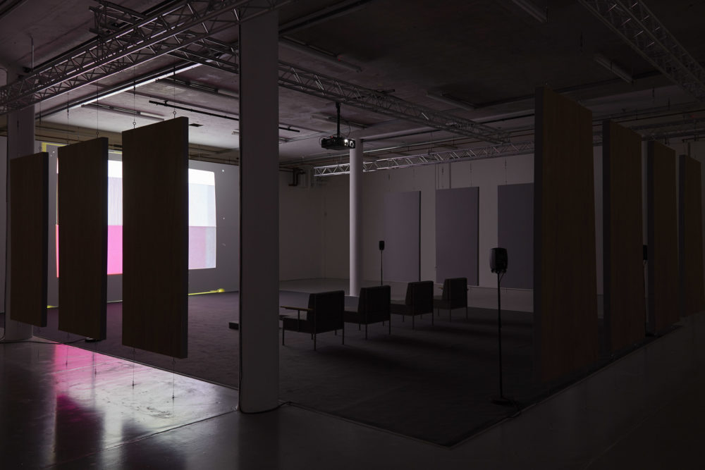 Four large chairs sit on a carpet square in the middle of the gallery. They face a screen that is obscured in this shot by some soundproofing boards that are hanging from the ceiling and framing the seating area.