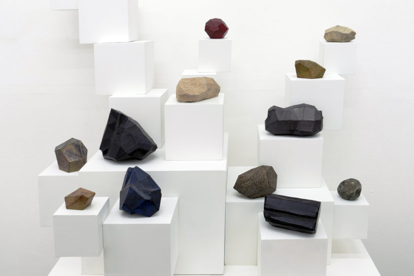 Installation: Rocks of varying sizes are placed on white plinths, also of varying sizes.