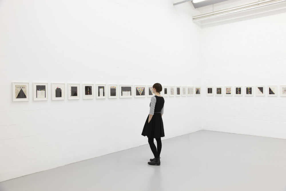 Installation view of David Batchelor Flatlands (2013). A visitor looks at several small works in white frames.