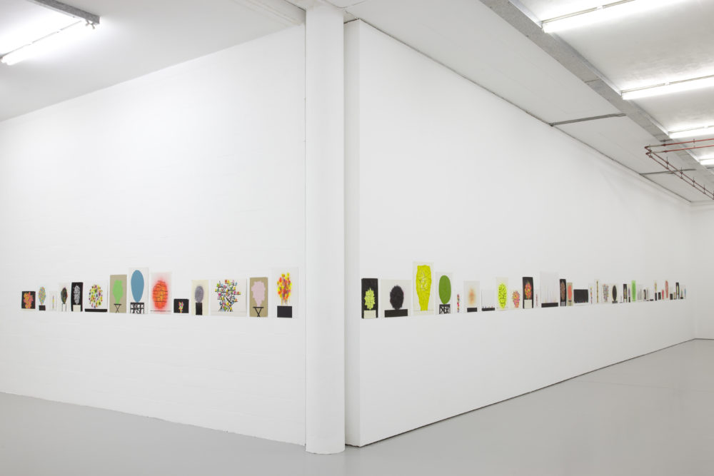 Installation view of David Batchelor Flatlands (2013). Small colourful prints hang on the gallery walls.