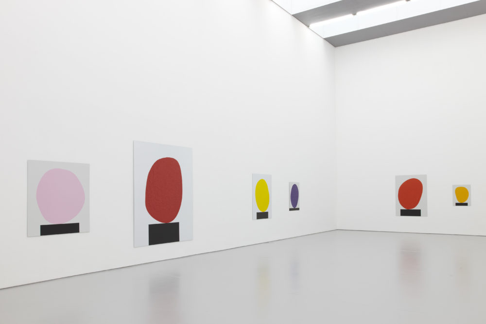Installation view of David Batchelor Flatlands (2013). Each work is a painting of a blob balancing on a black rectangle.
