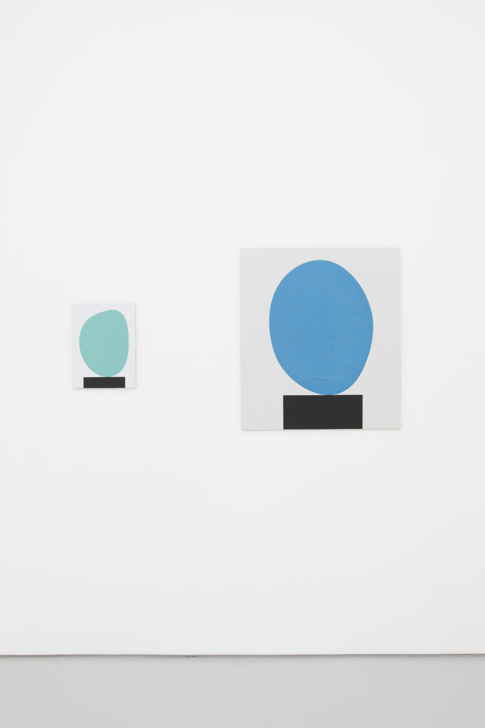 Installation view of David Batchelor Flatlands (2013). Two works side by side. Each work is a painting of a blue blob balancing on a black rectangle.