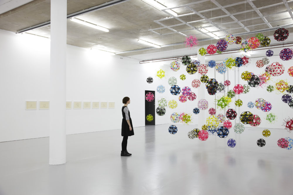 Installation view of David Batchelor Flatlands (2013). A visitor looks at plastic balls suspended from the ceiling.