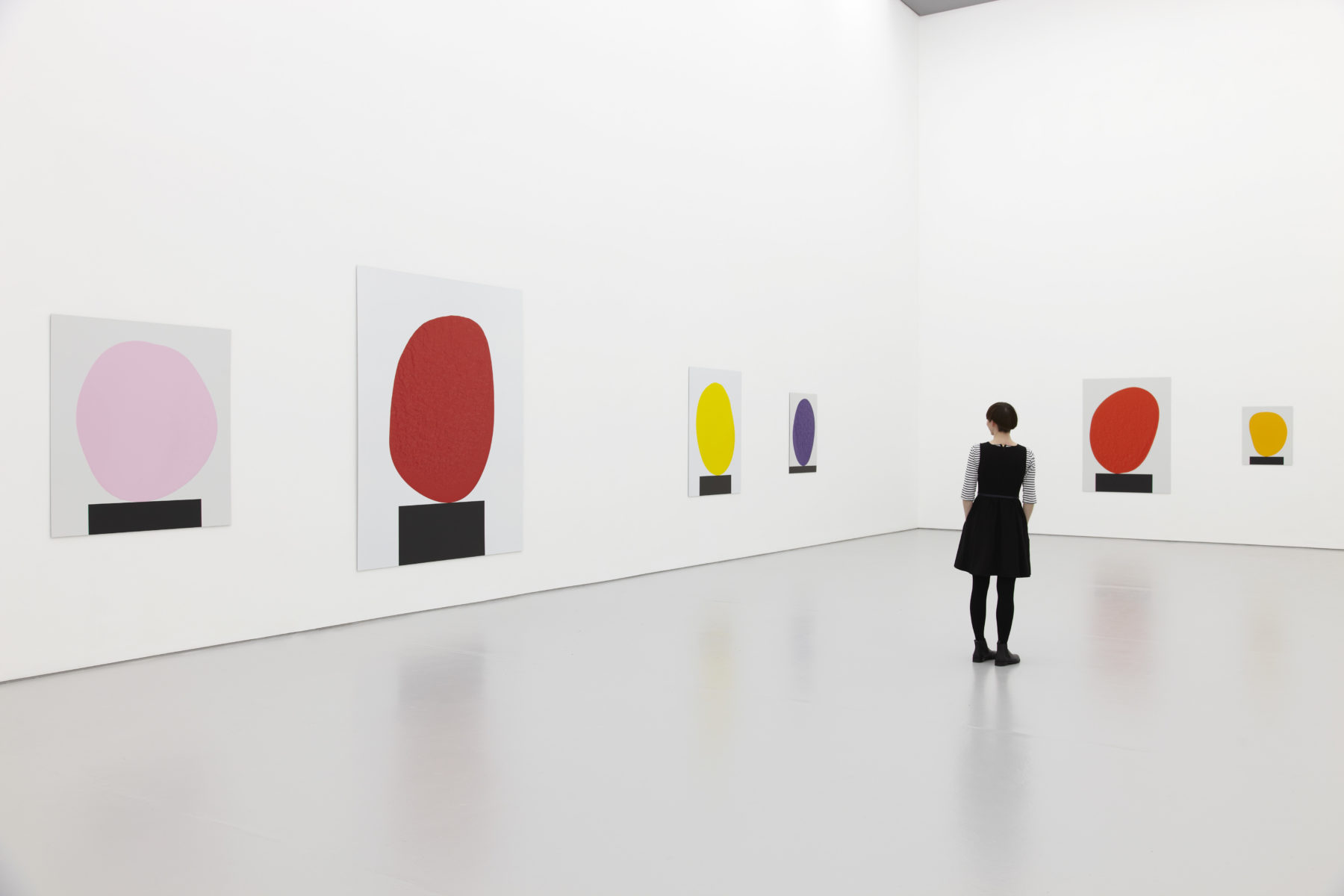 Installation view of David Batchelor Flatlands (2013). A visitor looks at images of coloured blobs balancing on black rectangles.
