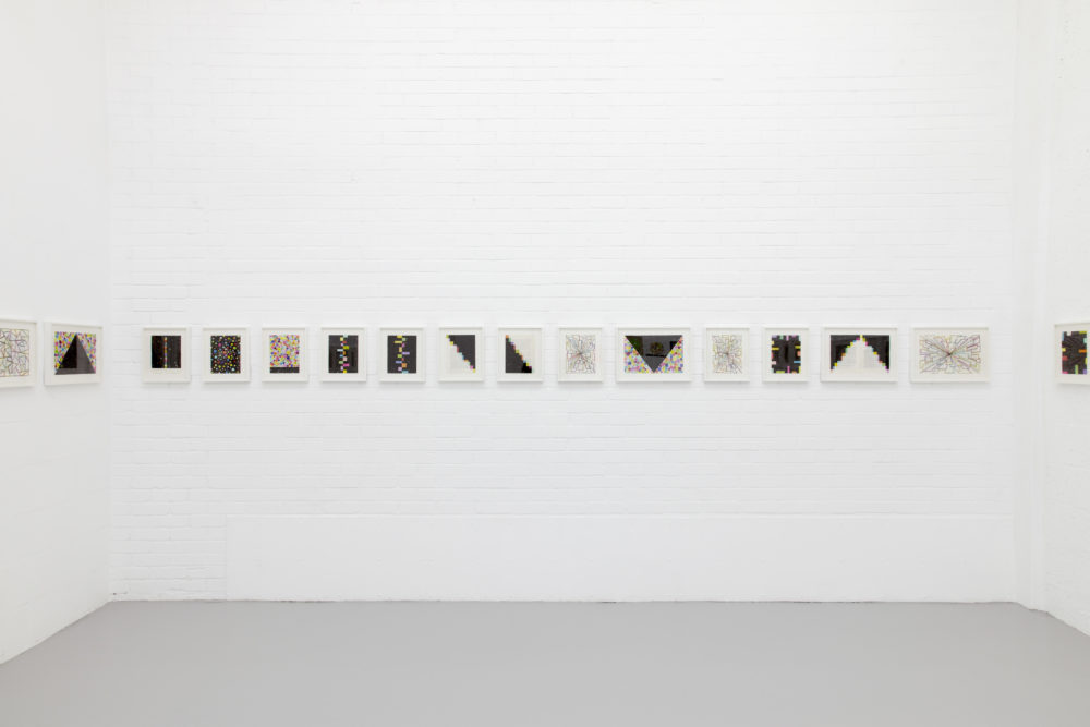 Installation view of David Batchelor Flatlands (2013). Small images are hung in white frames on white walls.