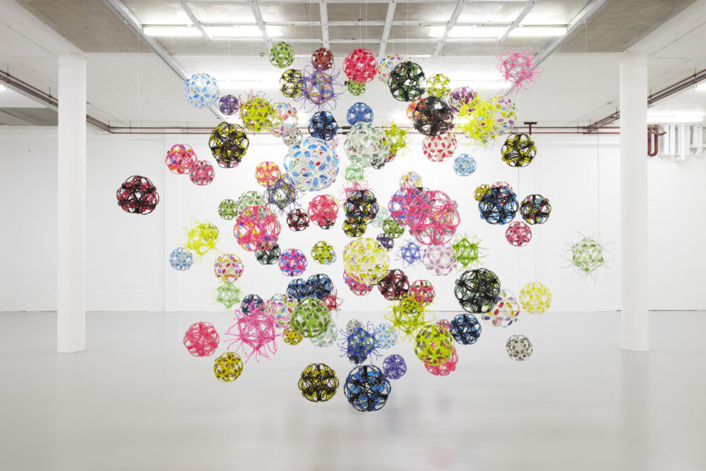 Installation view of David Batchelor Flatlands (2013). Various plastic balls are suspended from the ceiling.