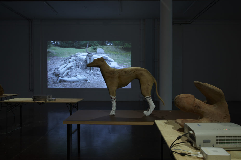 Installation view of Crêpe Suzette, (2012). A wooden carving of a whippet stands on a table and is wearing white sports socks.