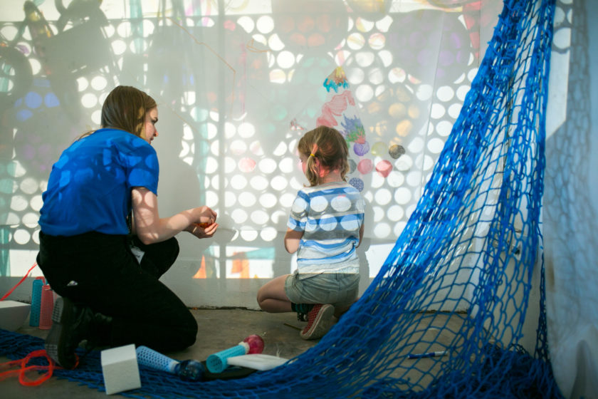 A creative family workshop using light and colour. The artist interacts with a young girl.