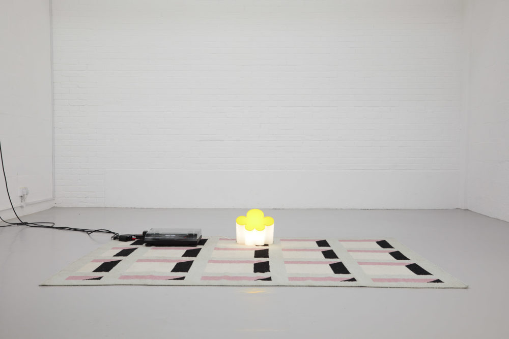 A rug, decorated to look like a building facade with lots of windows lies in the gallery. On top of it is a light in the shape of a cloud and a vinyl record player.