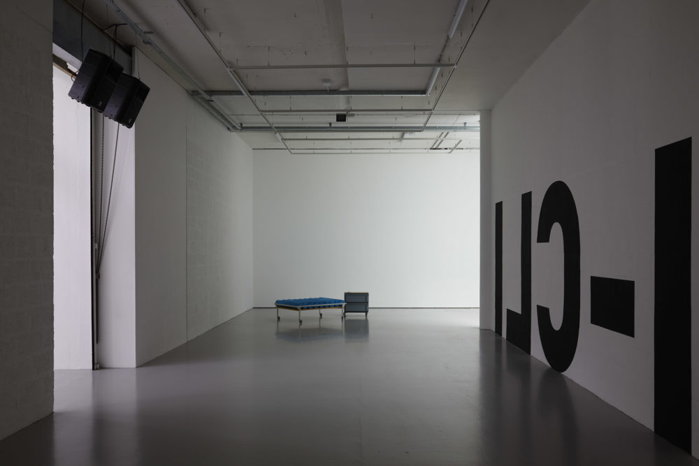 A corridor - on the right wall are large black letters written backwards. On the left wall are two large speakers. Directly in front is a medical-looking bench with a filing cabinet next to it.