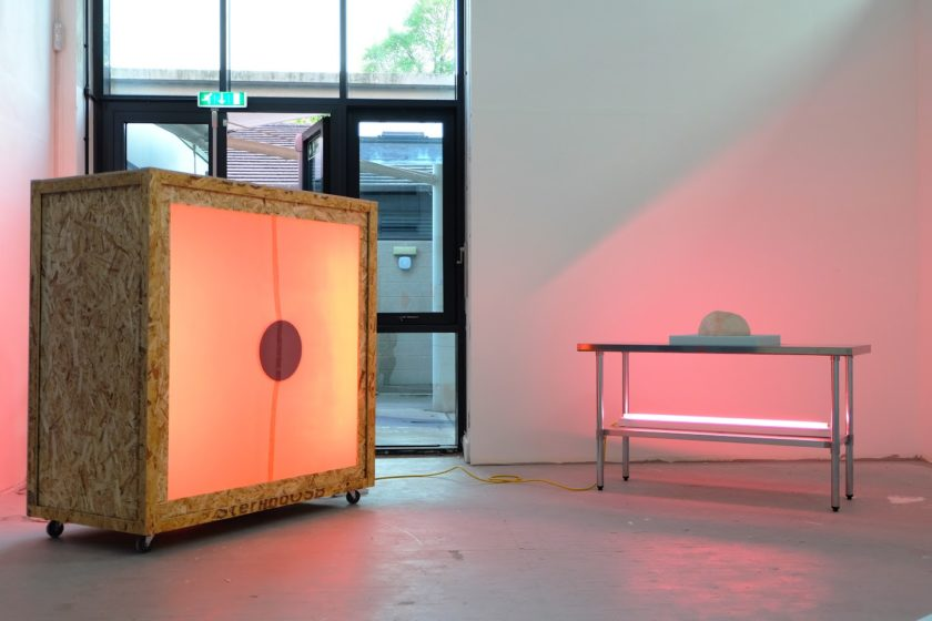 A cabinet is made from OSB and stretched canvas, a light comes from it shining through the canvas.