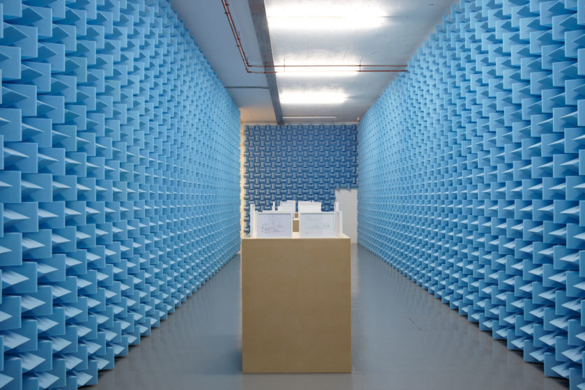 Installation view of Haroon Mirza. Small framed diagrams sit on wooden plinths in between walls covered in blue sound proofing foam.
