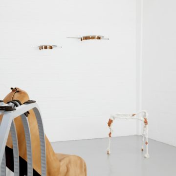 Installation: A metal frame used for displaying cars at show rooms shows in the foreground, horseshoes are placed on top of it. In the corner is a white walking frame with what looks like clay stuck to it. Coming out from the wall above are metal rails that have leather keyrings dangling from them.