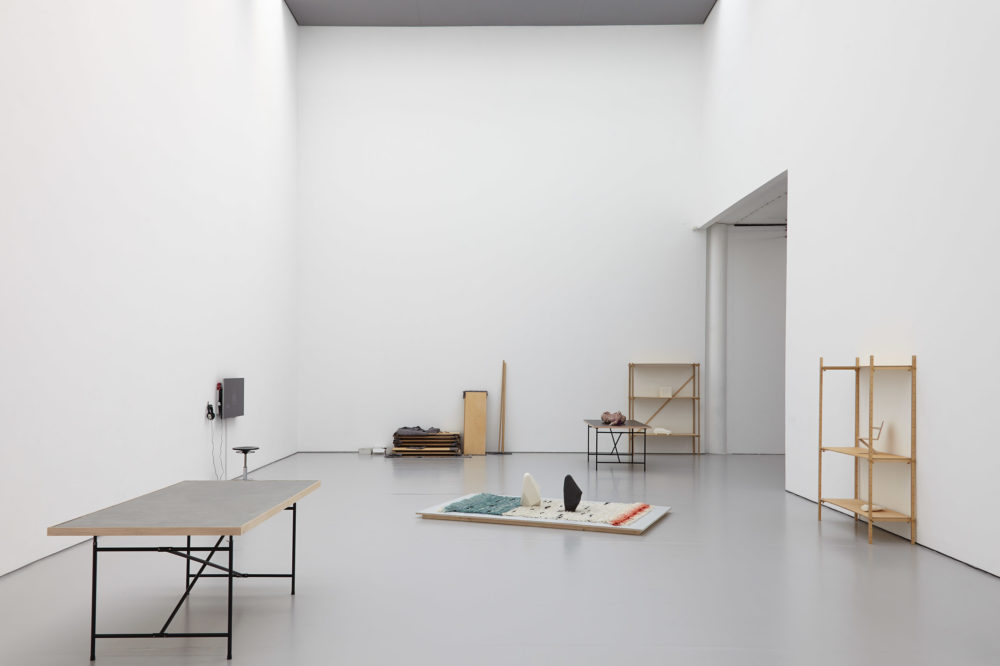 Various shelving units are place around the gallery giving an impression of a work in progress. In the middle of the gallery, on the floor is a rug with two vertical standing rocks on it.